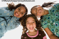 Children stock photo of three young multi-ethnic girls in a huddle looking down into camera.